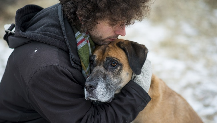 Young Caucasian man wearing a winter coat and a scarf hugging his pet dog lovingly to comfort him as they are out for a walk through a snowy forest during winter. The dog is a mixed breed and brown and black in color with a sad expression on his face.