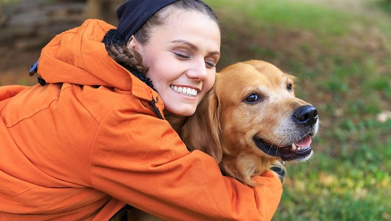 Smiling young woman kneeling and embracing a dog. Wears casual clothes, with eyes closed. Focus on foreground.