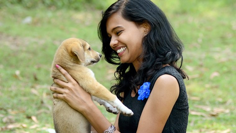 Young woman playing with puppy dog