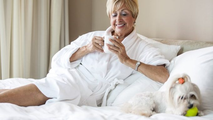 woman in robe on hotel bed with dog