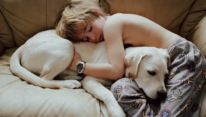 kid hugging dog on couch