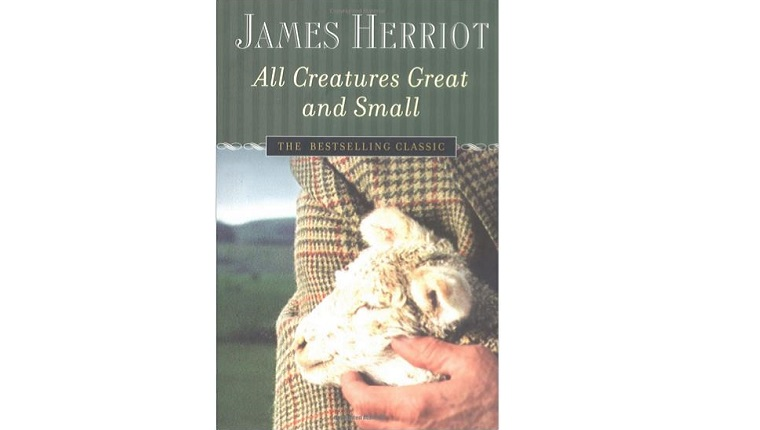 Cover art for All Creatures Great and Small. A man holds a lamb to his chest in the countryside.