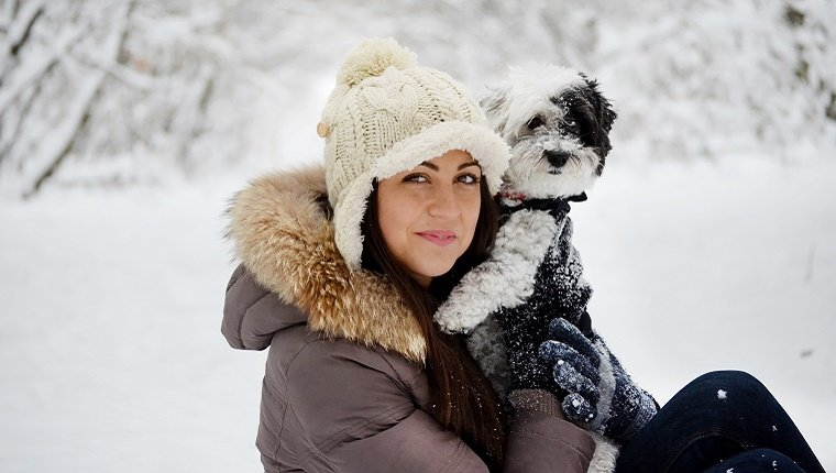 A young lady in winter gear holds a small dog with a jacket in front of a snowy forest background.