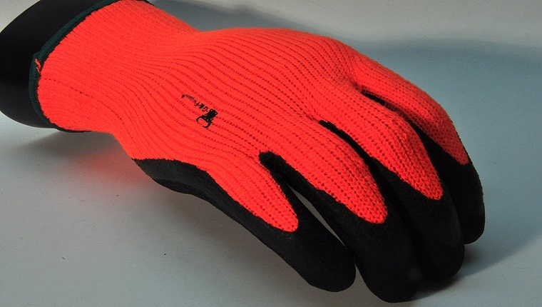 An orange glove with black gripping material on the fingers is displayed on a grey background.