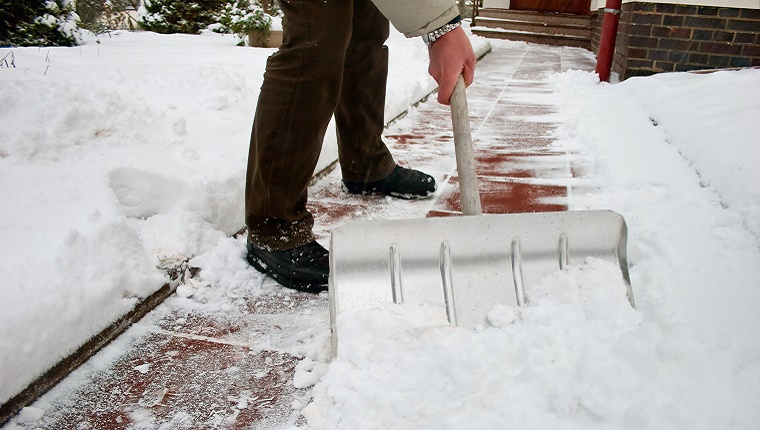 A man shovels snow off of the walkway in front of a building.