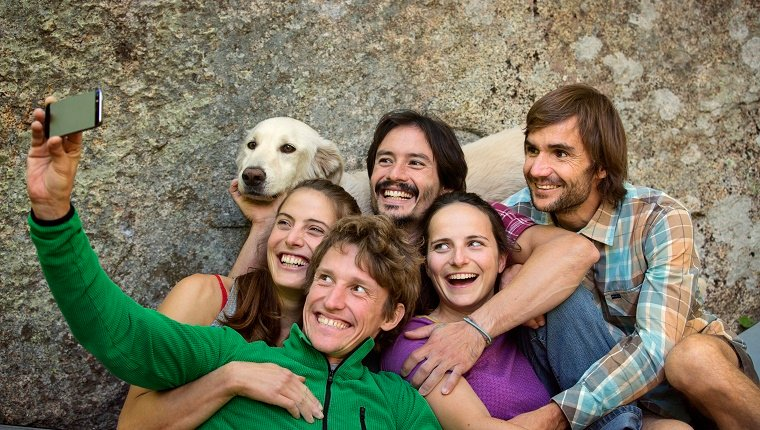 A group of hiking friends take a selfie with a Golden Retriever in front of a rock.