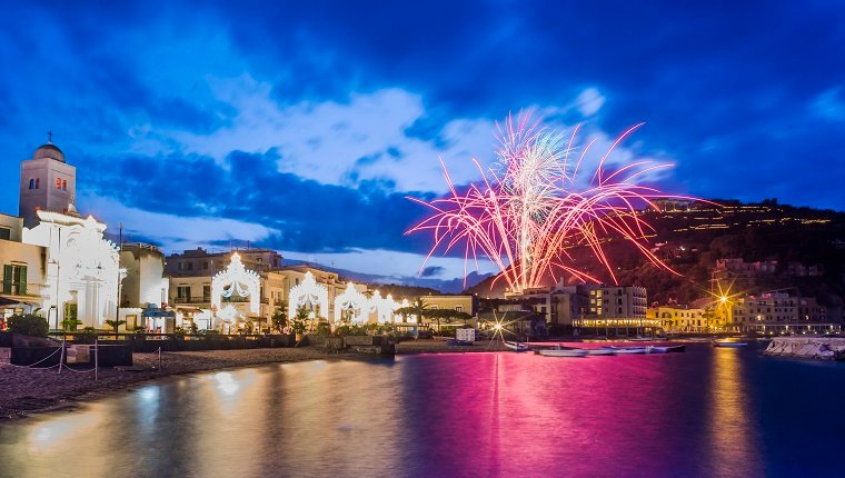 Colorful fireworks explode over a river next to a town in Italy.