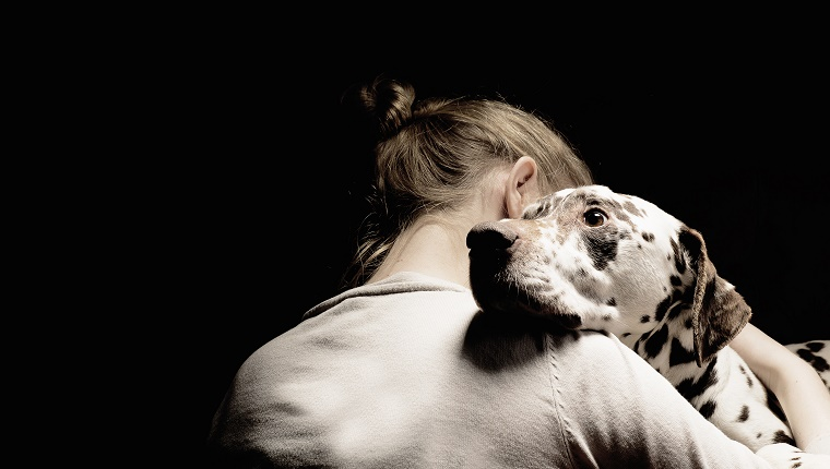 A girl hugs a black and white dog.