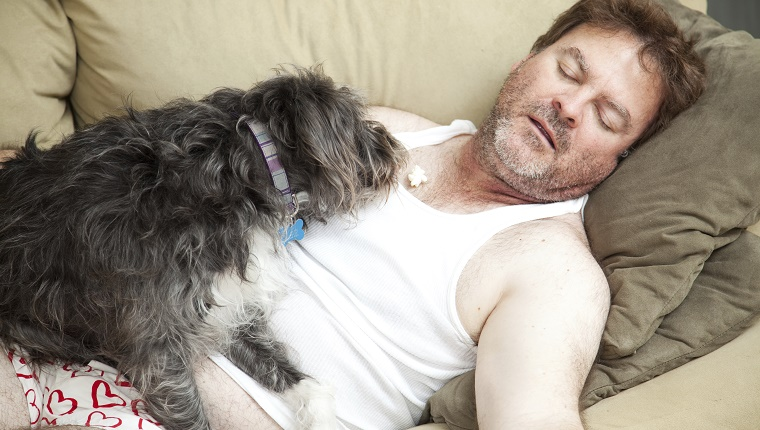 A man in his underwear lies on his couch while a dog lies on him and eats a piece of popcorn.
