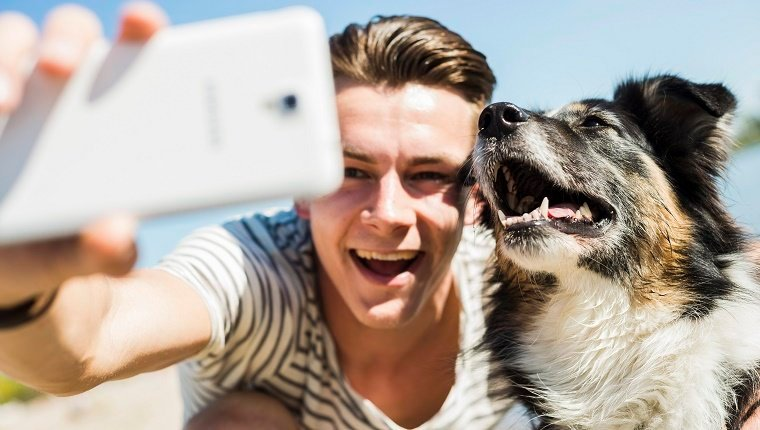 Happy young man taking selfie with dog outdoors