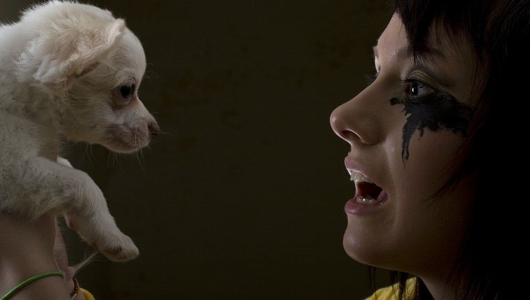 A woman with running eye makeup holds up her dog.