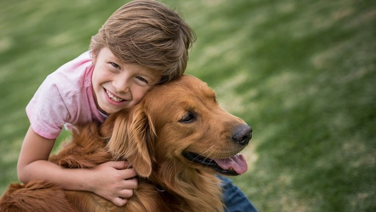Portrait of a happy boy outdoors with a beautiful dog - lifestyle concepts