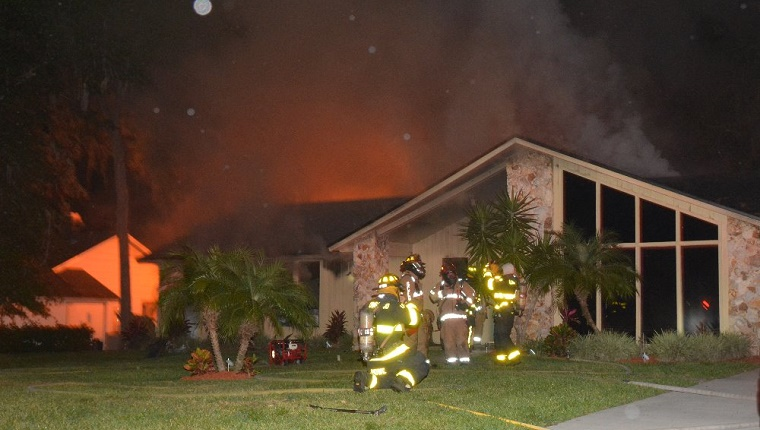 Firefighters stand outside the burning house.