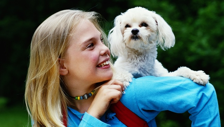 Girl (9-11) carrying Maltese terrier on back, smiling, close-up