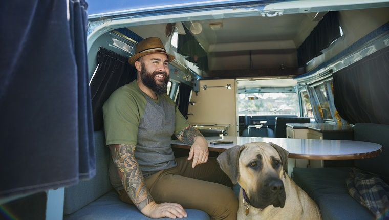 Smiling bearded man with dog in camper van