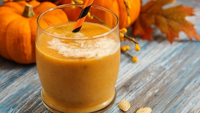 pumpkin smoothie with straw in front of fall decorations