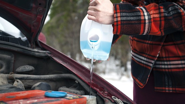 Closeup shot of hands holding bottle with antifreeze washer fluid and pouring it into windshield washer tank in winter day.