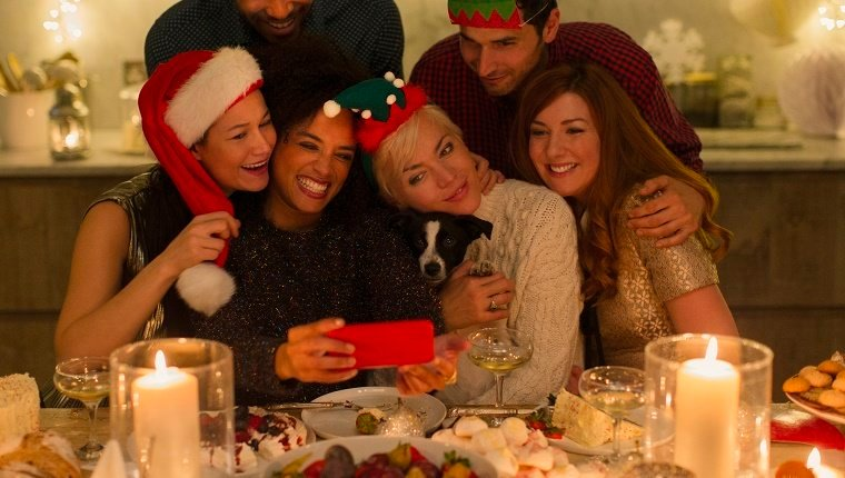 dog at table with family taking selfie at christmas