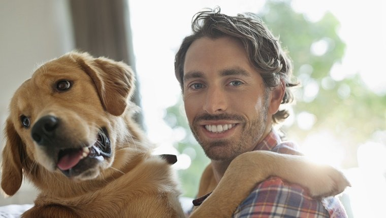 Smiling man petting dog indoors