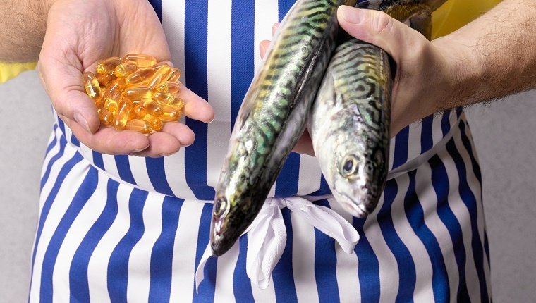 Fishmonger holding mackerel and Cod Liver oil tablets, close-up, mid section