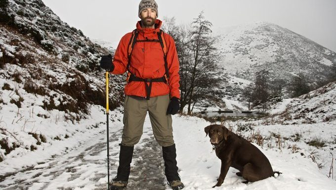 man and dog hiking in snowy mountains