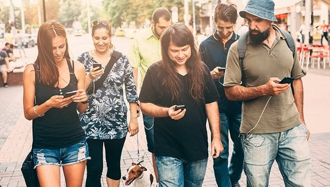 Friends walking dogs while on phones