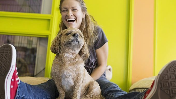 woman laughs with dog