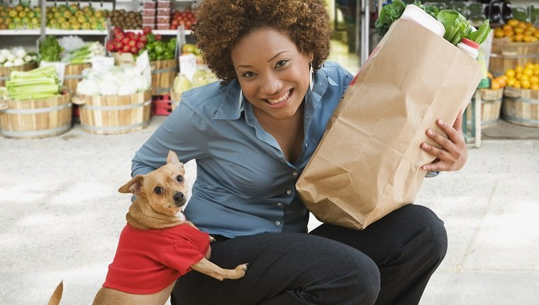 Hispanic woman with pet dog holding groceries