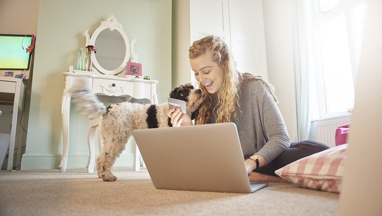 a young woman is sitting crosslegged on the floor of her bedroom using her laptop to buy something . she is holding her bank or credit card ready for the purchase . her family dog comes to say hello.