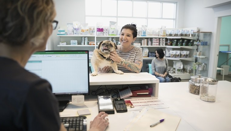Woman with dog checking in veterinarian clinic reception