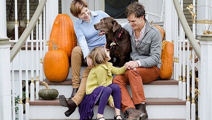family on stairs with dog and pumpkins