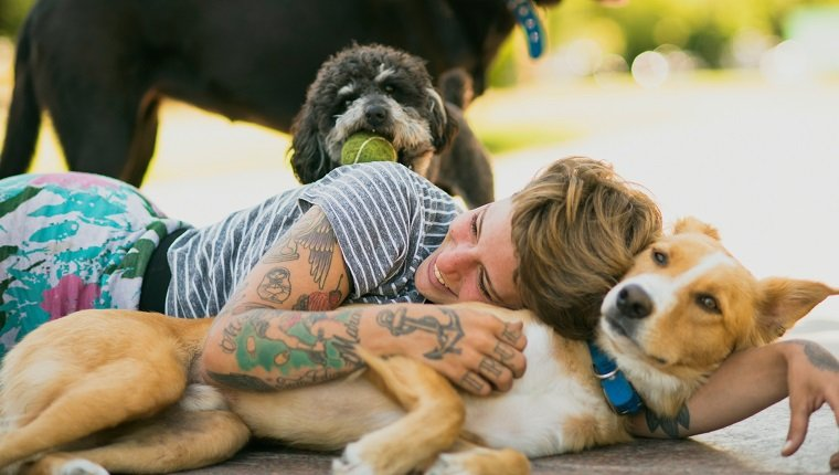 Tattoed woman relaxing with dogs at the park