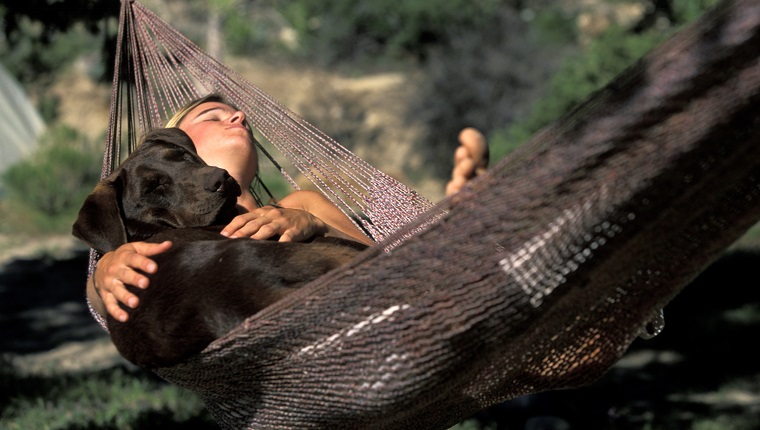 Young woman resting in hammock with her dog.