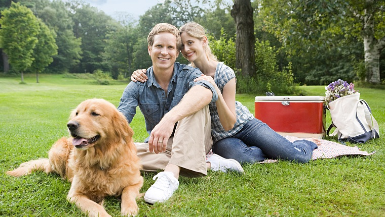 Couple having picnic with their dog