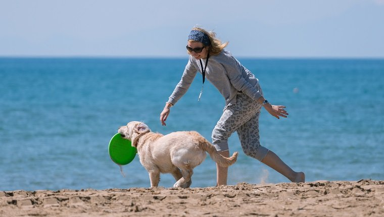 Happy women playing with her dog at the beach.