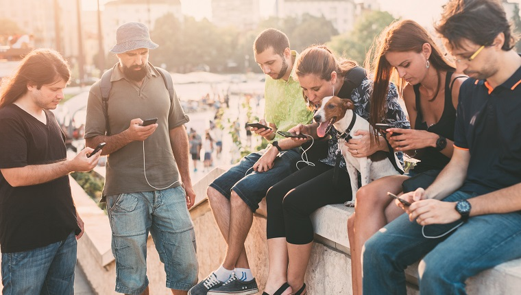A small group of people with a dog playing a game on their smart phones and sitting outdoor in the city center.