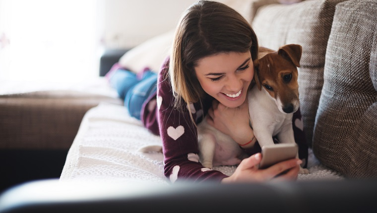 Beautiful woman using a mobile phone while lying with her dog.