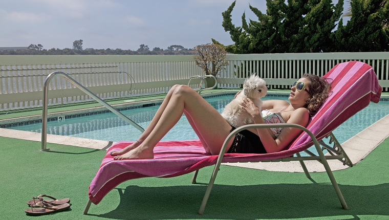 Woman laying down on lounge chair by swimming pool and holding dog on her stomach