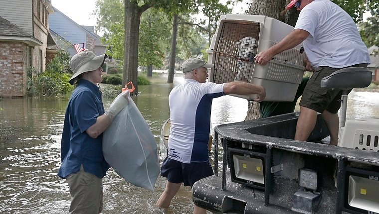 A father and son carry their dog as they evacuate from their homes the flood in Lakeside Estate in Houston, Texas on August 30, 2017. Monster storm Harvey made landfall again Wednesday in Louisiana, evoking painful memories of Hurricane Katrina's deadly strike 12 years ago, as time was running out in Texas to find survivors in the raging floodwaters. / AFP PHOTO / Thomas B. Shea (Photo credit should read THOMAS B. SHEA/AFP/Getty Images)
