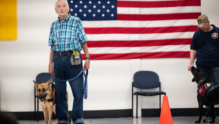 Michael Kidd, and his service dog Millie wait for their training at the Paws of War office in Nesconset, Long Island, New York on June 10, 2019. - The service dogs are either trained or being trained to help veterans through difficult times by Paws of War, an association funded entirely by private donations that provides the shelter animals free of charge.