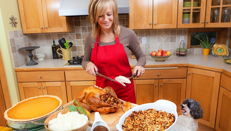 Woman preparing traditional Thanksgiving and/or Christmas dinner together. Carving a roast turkey on a cutting board in the family kitchen.