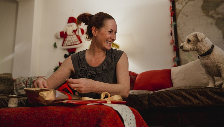 Mature woman wrapping Christmas presents at home.