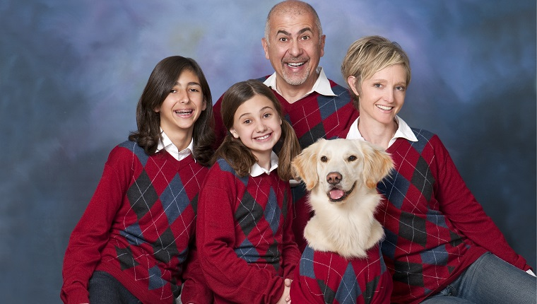 Humorous family portrait with golden retriever dog all in cardigans.