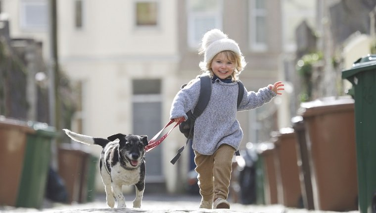 Young child running with dog