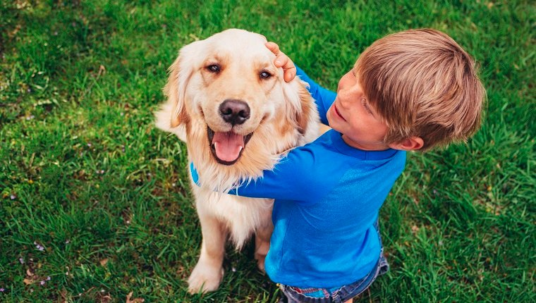 Smiling Boy sitting in garden stroking his golden retriever dog
