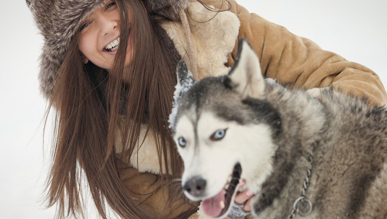 Portrait of happy woman with Siberian Husky during winter