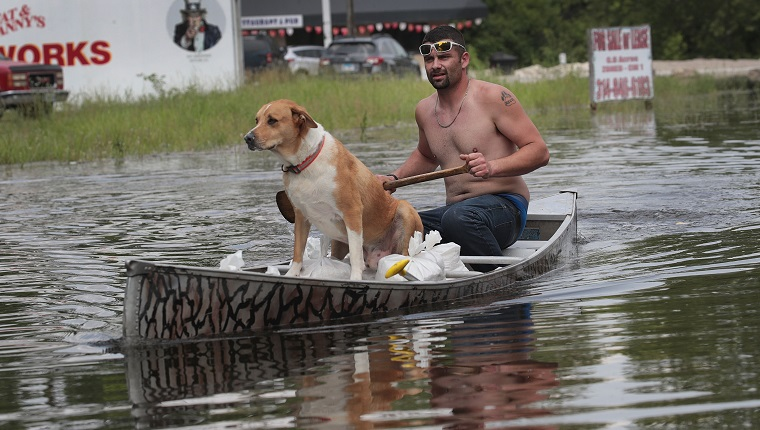BARNHART, MISSOURI - MAY 31: Ryan Sizemore paddles down Highway 61 with his dog Rico as he hauls sandbags to his home to hold back rising floodwater from the Mississippi River on May 31, 2019 in Barnhart, Missouri. The middle-section of the country has been experiencing major flooding since mid-March especially along the Missouri, Arkansas, and Mississippi Rivers. Towns along the Mississippi River have been experiencing the longest stretch of major flooding from the river in nearly a century.
