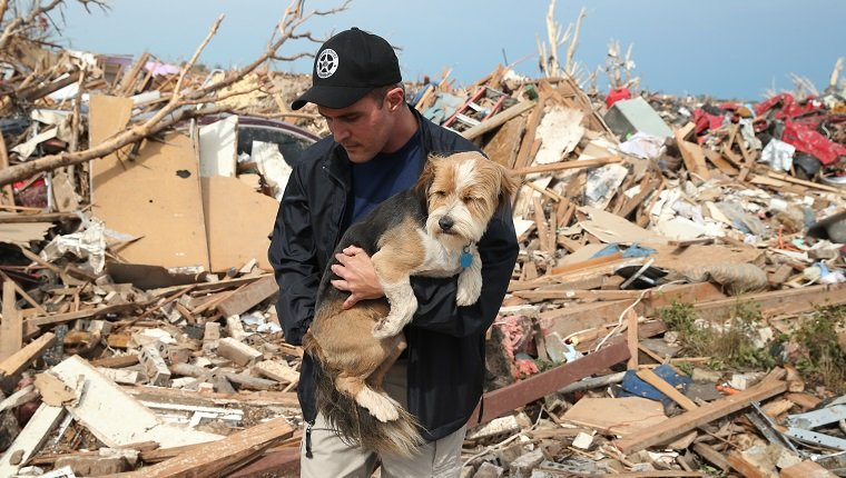MOORE, OK - MAY 21: Sean Xuereb recovers a dog from the rubble of a home that was destroyed by a tornado on May 21, 2013 in Moore, Oklahoma. The town reported a tornado of at least EF4 strength and two miles wide that touched down yesterday killing at least 24 people and leveling everything in its path. U.S. President Barack Obama promised federal aid to supplement state and local recovery efforts.