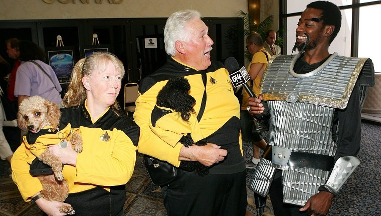 "LAS VEGAS - AUGUST 17: Pat Krob (L) and her husband Ken Krob of California hold their poodles named ""Lt. Tasha Yar"" (L) and ""Mr. Data"" as they are interviewed by G4TV correspondent William O'Neal of California at the fifth annual official Star Trek convention at the Las Vegas Hilton August 17, 2006 in Las Vegas, Nevada."