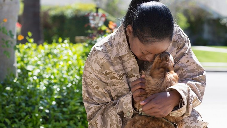 Female soldier hugging pet dog on street at homecoming